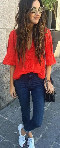 red bell sleeve v neck blouse with dark blue skinny jeans