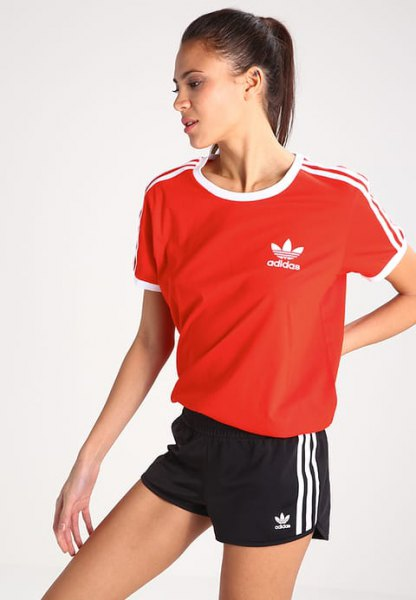 red t shirt with black mini sports shorts