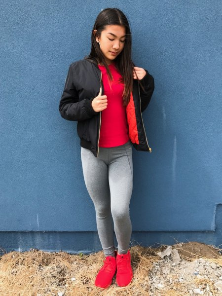 red tee with black bomber jacket and grey leggings