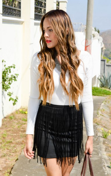 white long sleeve form fitting tee with black mini bodycon fringe skirt
