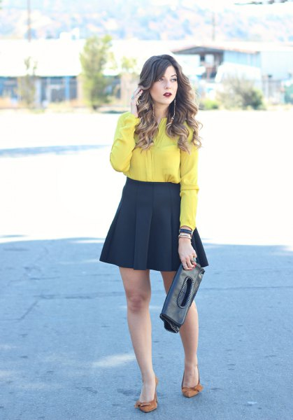 yellow button up shirt with black mini flared and pleated skirt