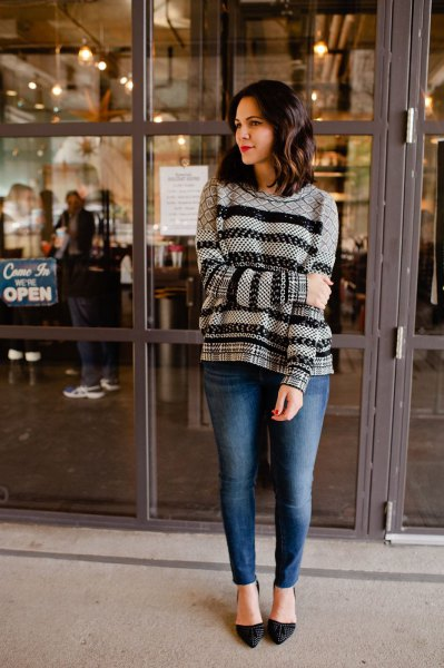 black and grey printed holiday sweater with blue slim fit jeans