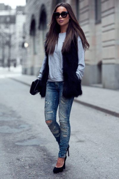 black faux fur vest with grey sweatshirt and ripped slim fit jeans