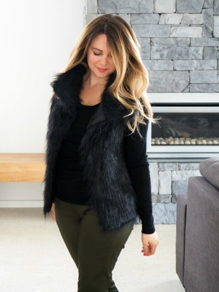 black scoop neck long sleeve t shirt with fur vest and grey slim fit jeans