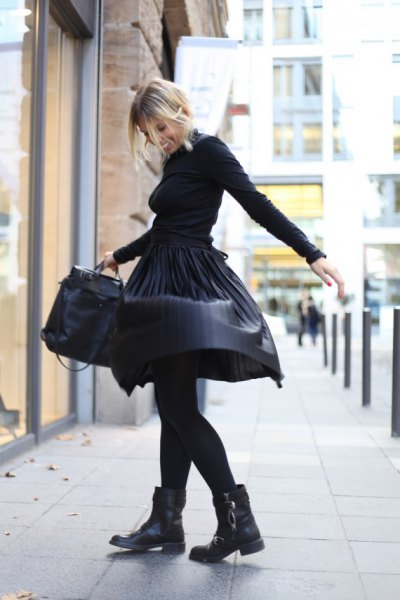 black sweater with matching leather pleated midi skirt and motorcycle boots