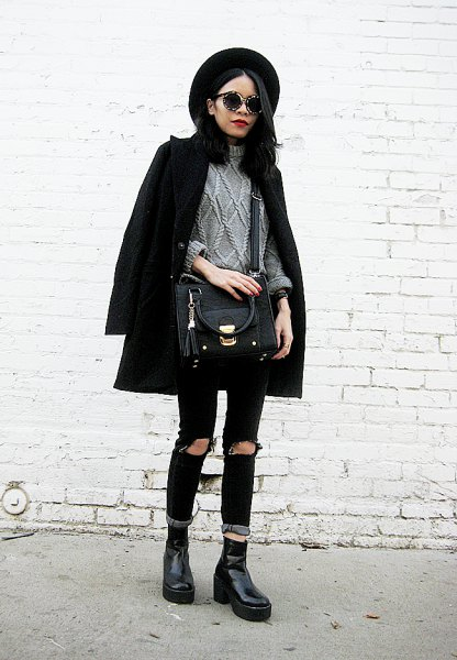 black wool coat with grey cable knit sweater and ripped jeans