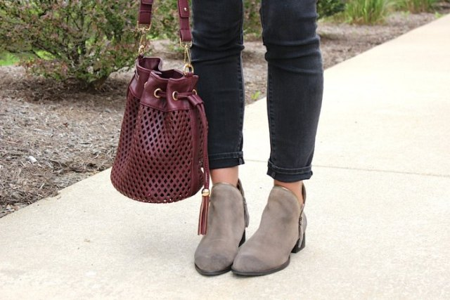 burgundy soft leather handbag with white blouse and black slim fit ankle jeans