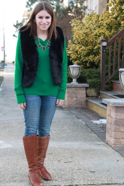 green sweater with black vest and camel suede knee high boots