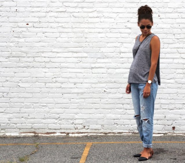 grey sleeveless scoop neck sweater with relaxed fit light blue jeans