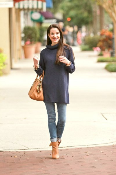 navy blue long sleeve turtleneck tunic with cuffed jeans and orange boots