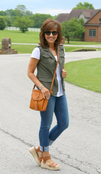 olive green utility vest with white tee and cuffed skinny jeans
