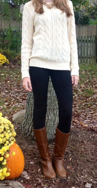 white cable knit sweater with black leggings and brown leather knee high boots