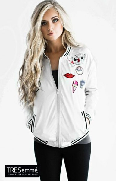 white embroidered bomber jacket with black tank top and skinny jeans