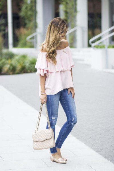white off the shoulder ruffle blouse with blue jeans and pink slip on loafers
