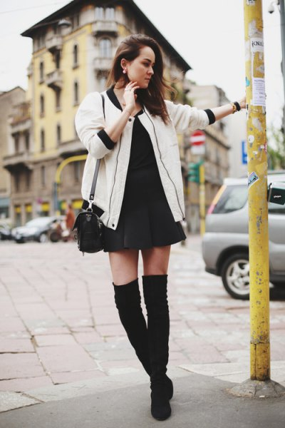 white oversized bomber jacket with black mini shift dress and thigh high boots