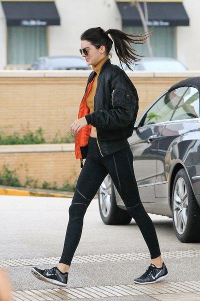 black bomber jacket with orange cropped mock neck sweater