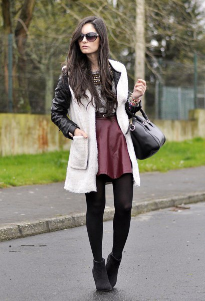 black leather jacket with white fleece long vest and maroon silk skater skirt