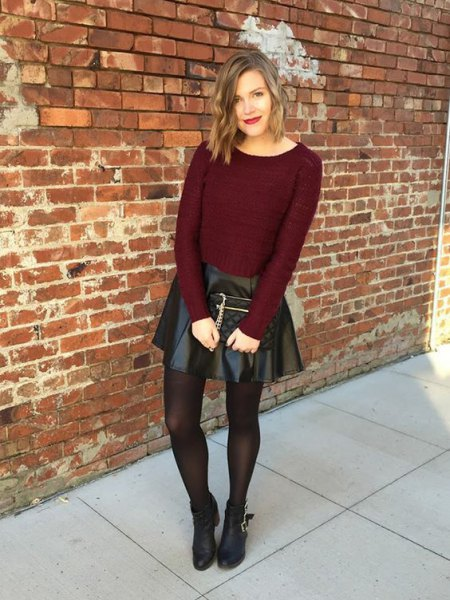 burgundy form fitting knit sweater with black leather mini skirt and brown stockings