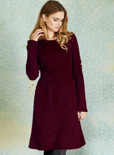 deep red belted long sleeve sweater dress with skinny jeans