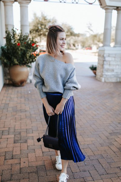 grey one shoulder sweater with dark blue pleated midi skirt