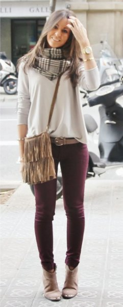 light grey sweater with skinny jeans and fringe shoulder bag