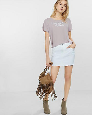 pink graphic tee with white mini denim skirt and suede boots
