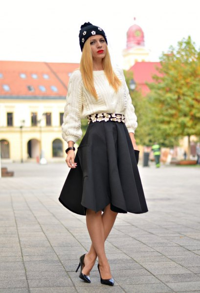white chunky knit sweater with black pleated skirt and heels