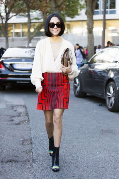 white v neck wrap sweater with red graphic skirt and mini boots