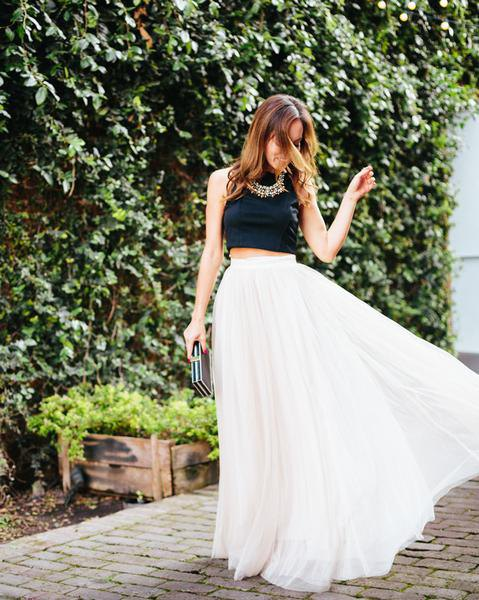 black cropped sleeveless top with white high waisted maxi pleated skirt