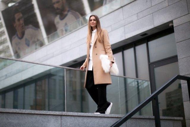 blush pink longline wool coat with black pants and faux fur white clutch handbag
