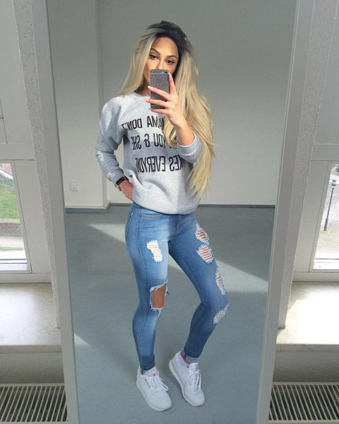 grey graphic sweatshirt with light blue ripped jeans