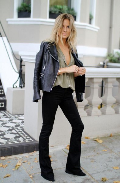 leather jacket with grey v neck blouse and black flared jeans