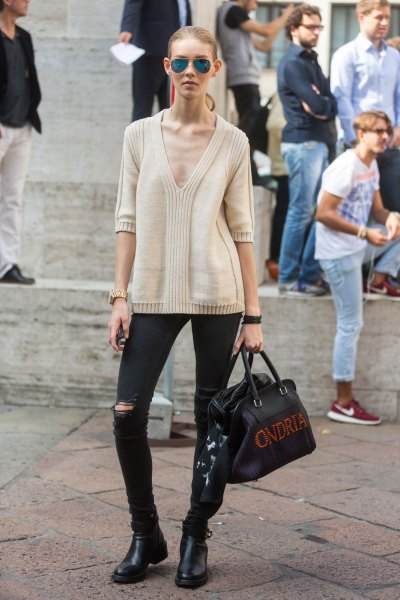 pale pink deep v neck pullover sweater with black ripped jeans and short boots