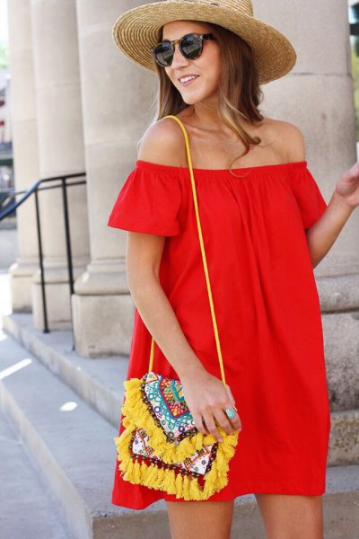 red off the shoulder blouse dress with yellow tribal printed purse