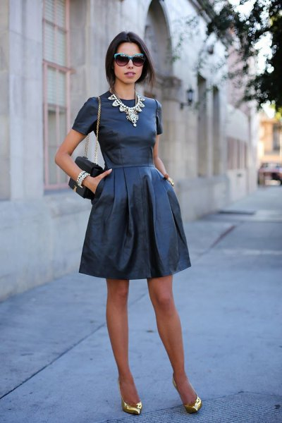 black fit and flare mini leather dress with gold pointed toe evening shoes