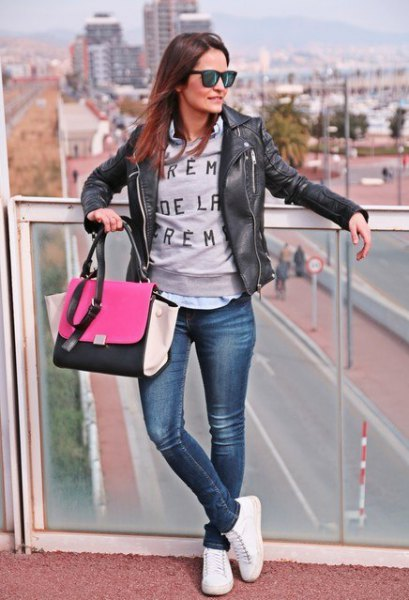 black leather jacket with grey graphic sweater and white tennis shoes