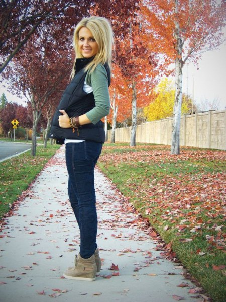 black quilted vest with dark blue skinny jeans and suede boots