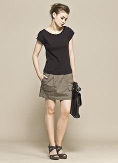 black t shirt with green mini cargo skirt and flat sandals