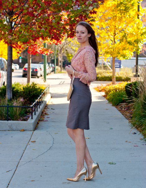 blush pink chiffon blouse with grey knee length skirt and gold heels