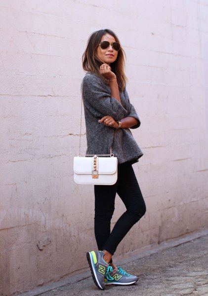 grey fleece pullover with white purse and black skinny jeans