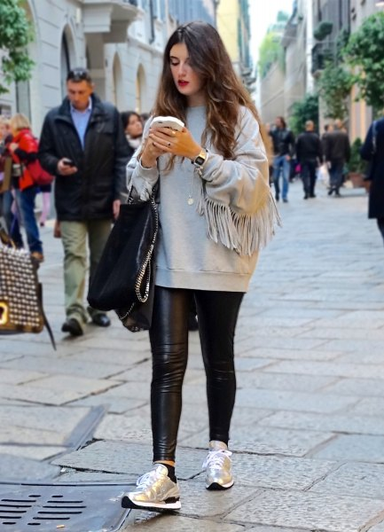 grey sweatshirt with black skinny leather pants and gold running shoes