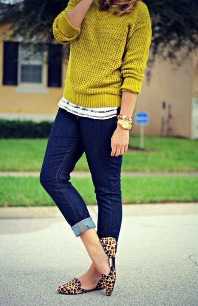 mustard yellow sweater with dark blue cuffed skinny jeans and animal print flat shoes