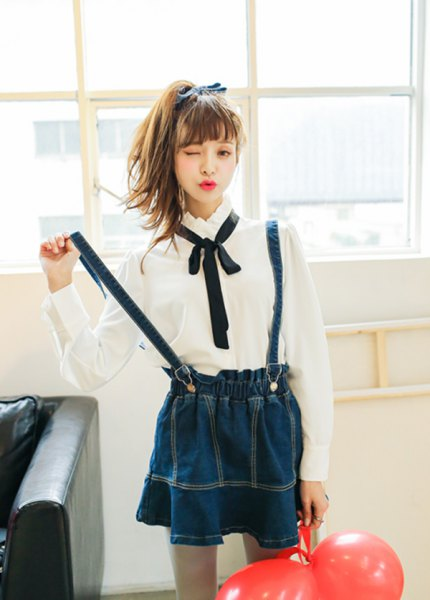 white button up shirt with black bow tie and navy pleated suspender skirt