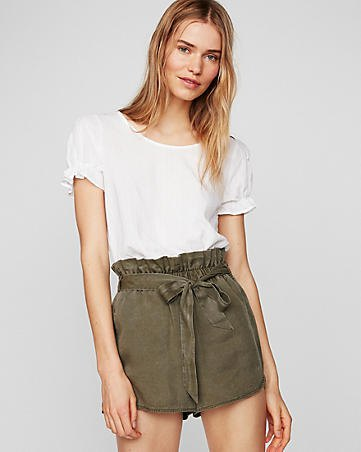 white cuffed t shirt with green tie high rise shorts