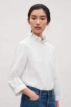 white mock neck blouse with blue skinny jeans