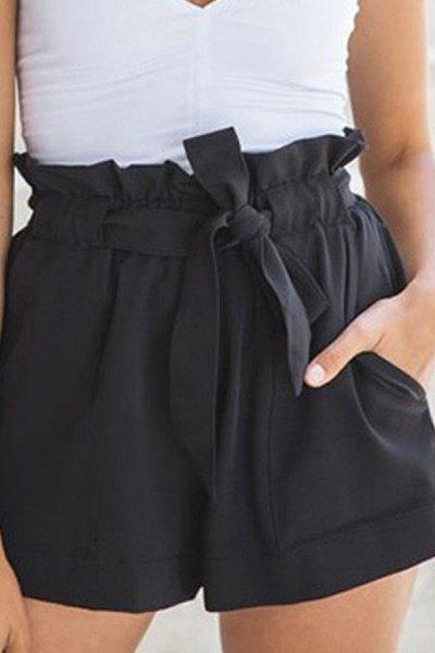 white v neck form fitting sleeveless blouse with mini black shorts