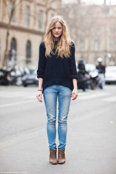 black chunky sweater with light blue slim fit jeans and tan ankle leather boots