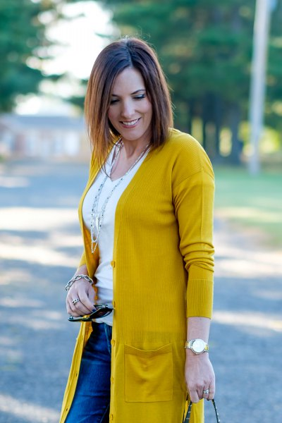 mustard yellow cardigan sweater with white scoop neck tee and blue jeans