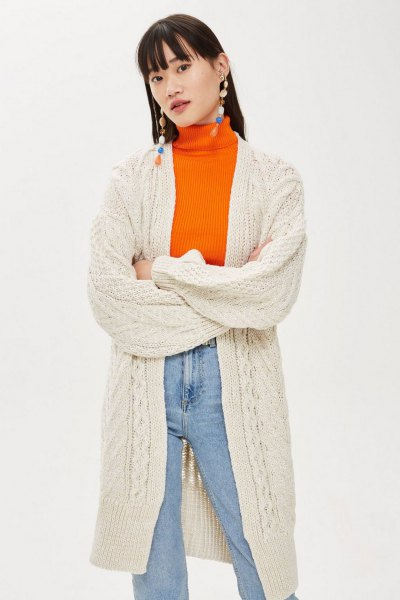 off white cable knit long cardigan with orange sweater and mom jeans