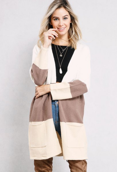 white and grey color block long cardigan with blue jeans and camel long boots